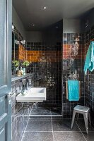 Black-tiled bathroom with shower area