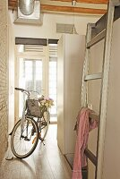 Bicycle and ladder leading to bed in bright entrance to loft apartment