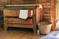 Old wooden trunk with drawers and basket against rustic wooden wall