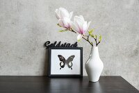 Magnolia flowers in white vase in front of picture of butterfly leaning against concrete wall