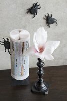 Magnolia flower in black candlestick, ornament made from folded paper and black beetle ornaments