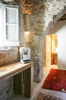 Rustic doorway in restored stone house with view into illuminated bathroom