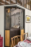Open sliding doors with view into bedroom integrated into eclectic apartment