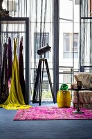 Feminine industrial style: colourful clothes on rail in front of industrial windows