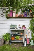 Gardening utensils, nesting boxes and plants against white board fence