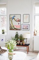 Vase of white wildflowers on marble coffee table and plant stand below black-framed pictures on wall in living area