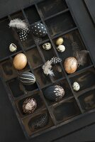 Variously painted eggs decorated with gilt, glitter and feathers in dark display case