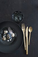 Place setting with gold cutlery, black plate and arrangement of eggs on glass plate