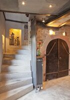 Concrete stairs leading down into cellar with arched door, niches and lighting