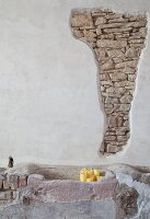 Rendered wall with section of exposed stone masonry, stone trough and candles