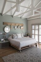 Mirrors hung from hooks on rustic wooden board in bedroom with exposed wooden roof structure