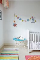 White cot, pale blue side table and pastel garland of elephants in nursery
