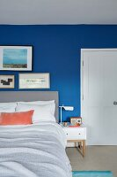 Gallery of pictures next to white panelled door in blue wall