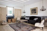 Black velvet sofa, vintage coffee table, easy chair and plain panelled wooden doors in living room