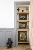 Framed photos and portrait on shelves in niche