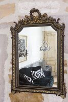 Black velvet sofa reflected in antique wall-mounted mirror