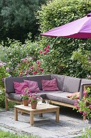 Lounge corner on small terrace between roses