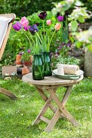 Tulips in green glass vases on garden table