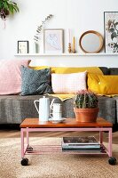 Retro crockery and cactus on coffee table with castors on sisal rug in front of grey couch with scatter cushions