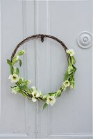 Rustic wreath made from rusty wire and tulips on cupboard door