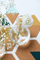 Delicate white rose and gypsophila in glass vases on hand-made cork coasters