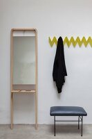 Yellow, zigzag, wall-mounted coat rack next to stool and simple mirror on stand with shelf
