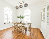 A white dining room with round arched windows and a covered dining table in an old building