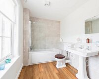 A bright bathroom with a washbasin, a toilet and a bathtub