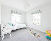 A white bed and colourful wooden toys on a grey carpet