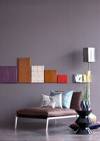 Canvases covered in high-tech fabrics on painted wall above leather couch and ceramic side table