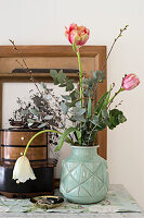 Bouquet of tulips, eucalyptus and branches in vintage vase