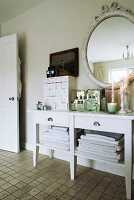 Vintage-style accessories on white console table in bathroom