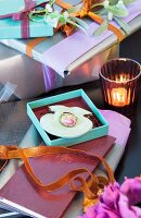 Lady's ring in turquoise gift box in front of stack of wrapped gifts