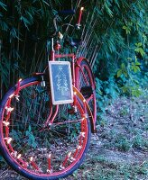 Red bicycle decorated with Christmas-tree candles and school slate in front of bamboo