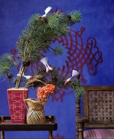 Bird decorations on pine sprigs in front of blue wall with red pattern