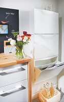 A plastic box for paper and a wooden crate for old bottles in a recycling corner of a kitchen with a white kitchen unit with a wooden countertop and ranunculus flowers in a vase