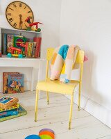 Patchwork knitted blanket on yellow chair and vintage toys in child's bedroom