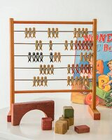 Retro abacus and building blocks in front of colourful picture books in child's bedroom
