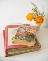 Retro children's books next to posy in beaker on white children's table