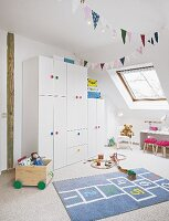 A white wardrobe with colourful handles and a hopscotch rug in a light and bright young girl's bedroom with slanted roof