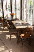 Old wooden tables and chairs with turned legs on rustic board floor next to glass wall