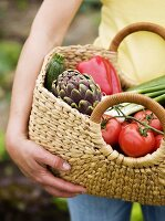 Woman holding bag of freshly picked vegetables in garden