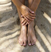 Woman sitting in sand (close-up of hands and feet)