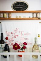 Bottles of drinks and flowers in a mug in front of a cloth embroidered with a motto with a wooden spice shelf above