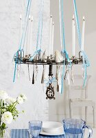 Silver spoons hanging from chandelier above dining table