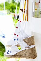 Knitted flower-power style espadrillos hanging on a door handle