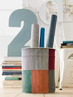 Rolls of paper in striped bin in front of stacked books and decorative number