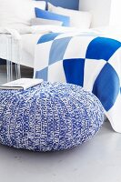 Pouffe with knitted cover and blue and white checked bed linen in bedroom