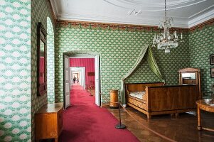 Schloss Corvey – bedroom with Biedermeier double bed and fabric canopy against a wallpapered wall