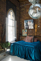Turquoise silk bedspread on French bed and disco balls in front of church windows in brick loft